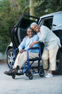 Senior couple with man in wheelchair next to car