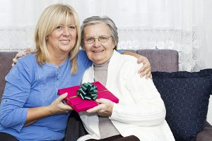 Smiling Mature nurse embracing  senior woman and holding a Christmas gift while sitting on the sofa.