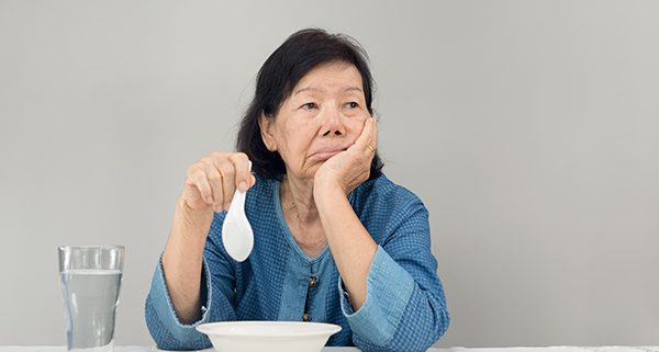 Elderly asian woman bored with food
