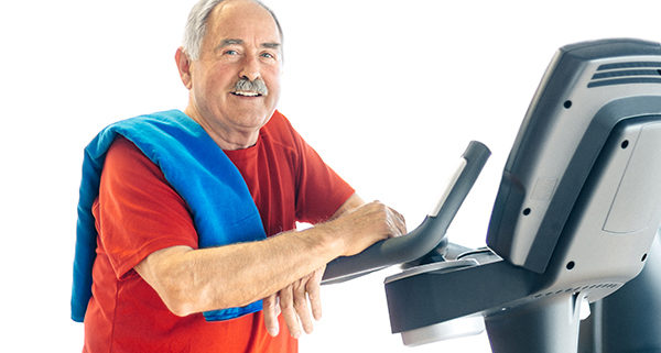 Healthy senior man in GYM leaning on spinning bicycle