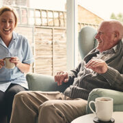 Senior man and female carer enjoying coffee at home