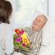 Stroke Recovery man smiling at woman with flowers