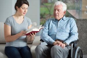 caregiver reading to senior living at home