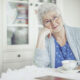 Elderly woman smiling while aging at home safely